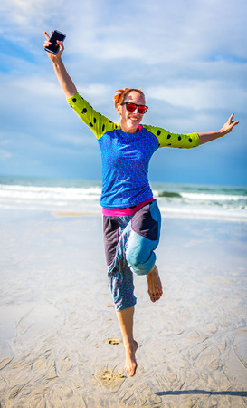 Woman running and jumping on beach with ocean in background. Mature young woman in colourful home made hippie clothes is jumping on the beach with smartphone in hand. Concept of success and freedom. Stock Photo