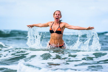 Woman enjoying the sea and waves of Atlantic ocean. Mature, mid aged, young attractive woman in bathing suit bikini is running in the ocean sea, playing and sprinkling the water. Atlantic ocean - Portugal. Stock Photo