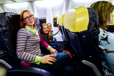 Family sitting on leather seats in commercial aircraft. Mother and daughters are sitting on a low cost airlines passenger jet plane.