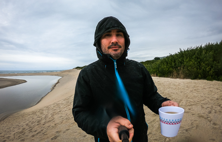 Man standing on sandy beach with selfie stick ocean background. Self portrait of man in rain clothes standing on Atlantic beach on a rainy day in wet rain clothes, cup of tea and selfie stick.