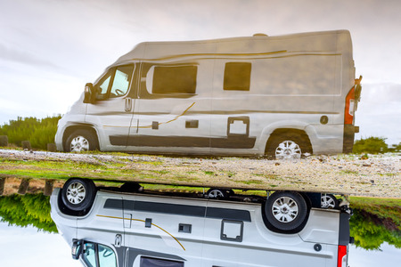 Campervan or motorhome camping on rainy day with rain puddles. Family vacation road trip with camper van, motor home or RV in with bad weather. Holiday travelling to Atlantic ocean - Spain or Portugal