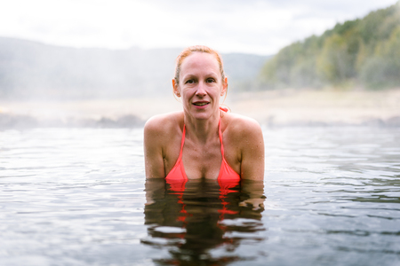 Woman relaxes and enjoys natural hot thermal water roman spa. Outdoor pools and baths with hot, smoking thermal water and hot spring of Aquis Querquennis - Bande, Galicia, Spain.