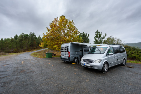 Campervan and motorhome camping on rainy day in nature parking. Family vacation road trip with camper van, motor home or RV in with bad weather. Holiday traveling to Atlantic ocean - Spain or Portugal