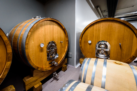Wooden wine barrels stacked in modern winery cellar in Spain. Modern, contemporary and traditional concrete wine cellar in wine factory - winery with oak barrels kegs with wine. Industrial production.