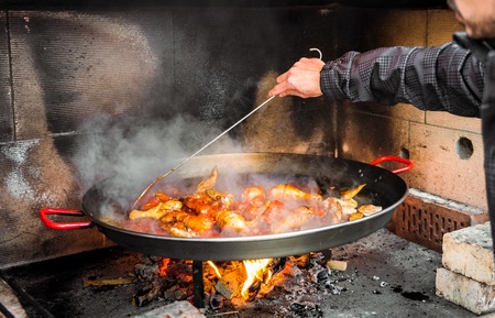 Cooking and making a traditional Spanish Paella over open fire. Traditional way of preparing Valencian paella  with fire wood and flames in a big pan. Made from Chicken and Rabbit meat in fireplace.