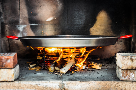 Cooking and making a traditional Spanish Paella over open fire. Traditional way of preparing Valencian paella  with fire wood and flames in a big pan. Preheating pan with hot flames.