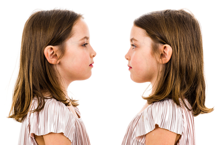 Identical twin girls are looking at each other being serious. Concept of family and sisterly love. Profile side view of identical twin sisters looking at each other. Studio shot isolated on white. Stock Photo