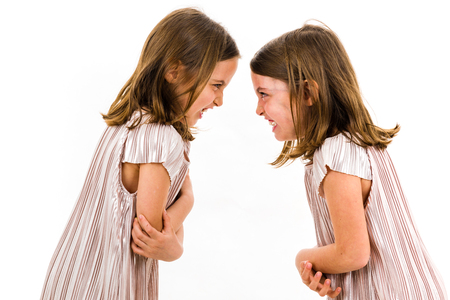 Identical twin girls sisters are arguing yelling at each other. Angry girls are shouting, yelling and arguing with emotional expression on faces. Frontal profile view of children. Isolated on white.