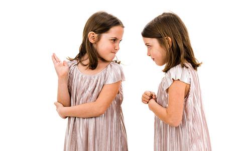 Identyczne siostry bliźniaczki kłócą się, krzycząc na siebie. Rozzłoszczone dziewczyny krzyczą, krzyczą i kłócą się z emocjonalnym wyrazem twarzy. Widok profilu czołowego dzieci. Na białym tle. Zdjęcie Seryjne