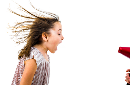Girl is yelling, shouting at blow dryer - hair dryer. Little girl not enjoying and yelling at blow dryer wind, when mother is drying her hair. Isolated on white background.
