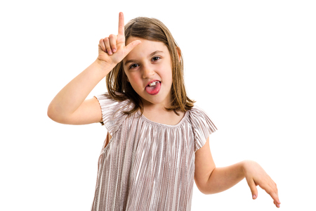 Portrait of happy girl making loser hand gesture at camera. Portrait of a cheerful cute little child girl looking at the camera, smiling showing L sign offensive gesture. Isolated on white background