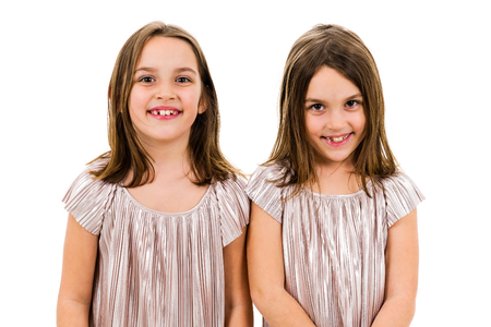 Identical twin girls sisters are posing for the camera. Happy twin sisters in dresses are looking at the camera and smiling. Frontal view, studio shot, isolated on white background.