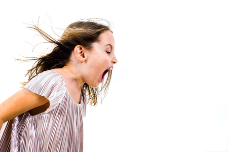 Little girl child yelling, shouting and screaming with bad manners. Angry upset girl is arguing with emotional expression on face. Frontal profile view of children. Isolated on white background. 版權商用圖片