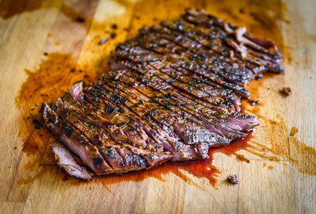 Sliced grilled juicy marinated angus beef flank steak on wooden board. Finished juicy medium rare meat is sliced and ready for serving. Professional gourmet restaurant style steak. Reklamní fotografie