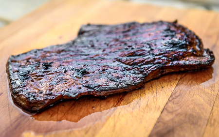 Grilled juicy marinated angus beef flank steak on wooden board. Finished juicy medium rare meat is resting before it is cut and sliced.