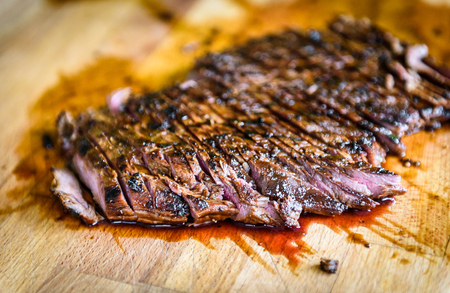 Sliced grilled juicy marinated angus beef flank steak on wooden board. Finished juicy medium rare meat is sliced and ready for serving. Professional gourmet restaurant style steak. 版權商用圖片