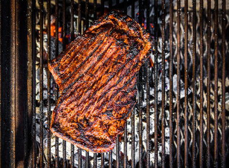 Grilling marinated angus beef flank steak on hot coals barbecue grill. Preparing juicy medium rare meat on hot grill BBQ with grill marks in restaurant fireplace.