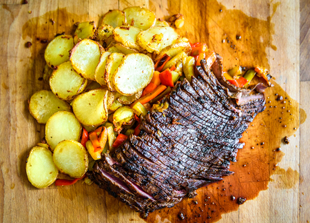 Sliced grilled juicy marinated beef flank steak on wooden board. Juicy medium rare meat is sliced and ready for serving with vegetables and baked potatoes. Professional gourmet restaurant style steak 版權商用圖片