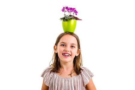 Girl carrying flower pot on head, having fun smiling. Little girl in dress holding green flower pot with viola flowers on her head having fun, goofing around. Studio shot isolated on white background 版權商用圖片