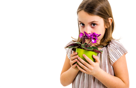 Sad young little girl holding flower pot mourning family loss. Child grieving over losing loved ones. Girl is looking at the flower pot, with sad face, crying. Profile view, studio shot, isolated on white background.