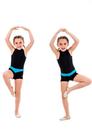 Des jumelles identiques pratiquent et font de la gymnastique rythmique, fond blanc. Les jeunes filles sœurs dansent et s'amusent à faire des exercices de gymnastique rythmique. Isolé sur fond blanc.