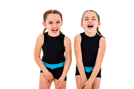 Portrait of identical twin girls dressed in rhythmic gymnastics dress. Young twin sister girls frontal portrait in dancing sports dress. Girls are smiling and having fun. Isolated on white background