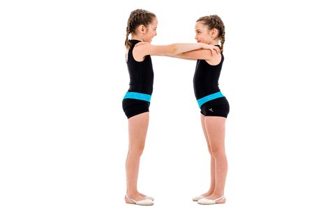 Identical twin girls practice and doing rhythmic gymnastics, white background. Young sister girls are dancing and having fun performing rhythmic gymnastics exercises. Isolated on white background.