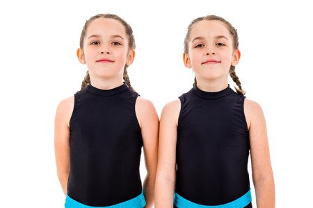 Portrait of identical twin girls dressed in rhythmic gymnastics dress. Young twin sister girls frontal portrait in dancing sports dress. Isolated on white background. 版權商用圖片