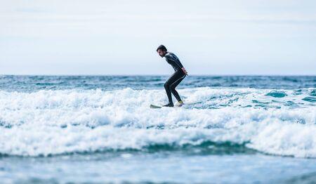 Surfer guy surfing with surfboard on waves in Atlantic ocean. Man in surfing wet suit is active surfing the waves of cold atlantic ocean in Galicia, Spain. 版權商用圖片
