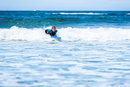 Surfer woman with surfboard is paddling on the wave. Girl in surfing wet suit is paddling the waves of cold atlantic ocean in Galicia, Spain. 版權商用圖片