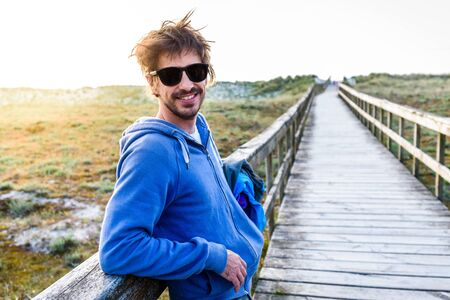 Hipster Spanish looking young man standing on sand beach. Young attractive man is standing on wooden bridge over sand dunes on Atlantic sandy beach in Spain or Portugal with sunset in background. 版權商用圖片
