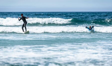 Young couple surfing with surfboard on waves in Atlantic ocean. Husband and wife or boyfriend and girlfriend are actively surfing the waves of cold atlantic ocean in Galicia, Spain. 版權商用圖片
