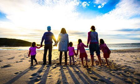 Family and friends group standing on the beach holding hands. Group of people, family, friends, adults and children are holding hands on the sandy beach watching the sunset on summer evening. 版權商用圖片