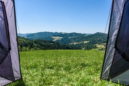 Camping tourist tent set up on meadow in the mountains. Small tent in green mountains of Slovenia. Discovering, hiking on active family vacation in nature with spectacular view of hills and forest. 写真素材