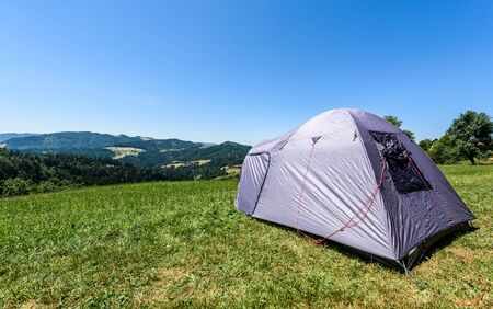 Camping tourist tent set up on meadow in the mountains. Small tent in green mountains of Slovenia. Discovering, hiking on active family vacation in nature with spectacular view of hills and forest.