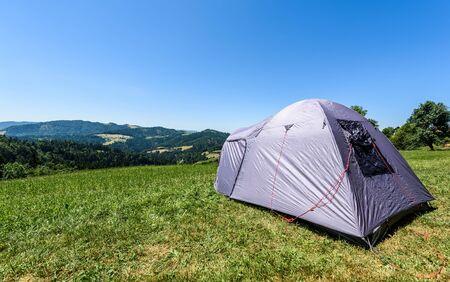 Camping Touristenzelt auf einer Wiese in den Bergen. Kleines Zelt in den grünen Bergen Sloweniens. Entdecken, Wandern im aktiven Familienurlaub in der Natur mit spektakulärem Blick auf Hügel und Wald.