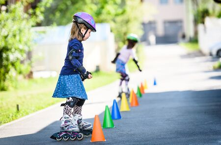 Children learning to roller skate on the road with cones. Twin girls are practising safe roller skating on a home driveway road wearing protective gear - helmets, knee, elbow and hand protectors or pads. Stok Fotoğraf