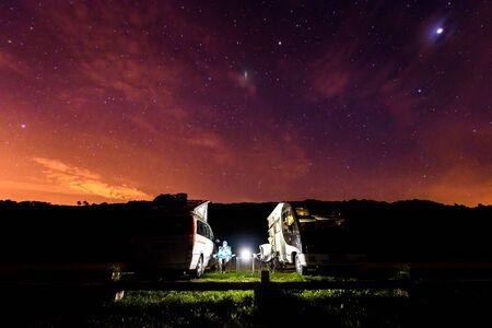 Wohnmobile werden nachts unter Sternen an einem Strand geparkt. Ein Mann, der mit zwei Wohnmobilen campt, genießt die abendliche Entspannung unter der Sternennacht am Strand von Soesto - Galicien, Spanien. Standard-Bild