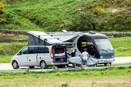 Motorhome RV and campervan are parked on a beach. Surfers on vacation are packing surfboards or boards after a day of wave surfing. Atlantic beach - Spain.