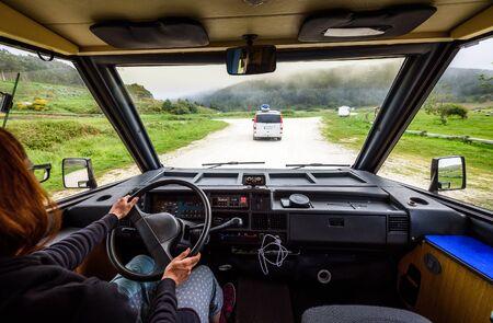 La mujer está conduciendo autocaravana o autocaravana en la carretera al aire libre en la naturaleza. Autocaravana es seguir una autocaravana en un viaje familiar de aventura o un viaje en la naturaleza en Galicia, España. Explorando en vacaciones activas