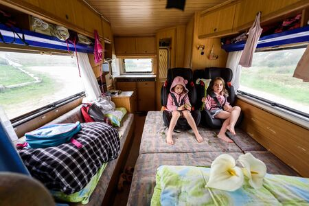 Children strapped in children safety seats when driving in motorhome. The interior of motorhome while driving on family vacation. Children safety while travelling. Reklamní fotografie