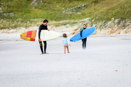 Surfing family with surfboard is walking on the sandy beach. Daughter is greeting parents after surfing session in atlantic ocean in Galicia, Spain. Mother, father and little girl on active vacation.