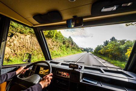 여자는 자연 속에서 야외 도로에서 모터홈이나 캠퍼밴을 운전하고 있습니다. Motorhome은 모험 가족 여행 또는 Galicia Spain의 자연 여행에서 캠퍼밴을 따라가고 있습니다. 활동적인 휴가 탐색