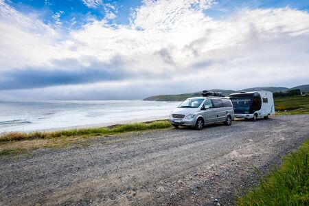 Motorhome RV and campervan are parked on a beach. Family on vacation is camping on the side of the road with amazing view of the beach and ocean. Atlantic beach - Spain.