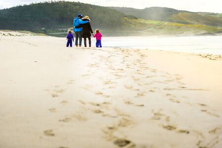 Happy young family is walking on sandy beach and ocean. Happy family - father, mother, baby girls hold hands, walking along sandy beach. Lifestyle photo of active parents traveling with children.