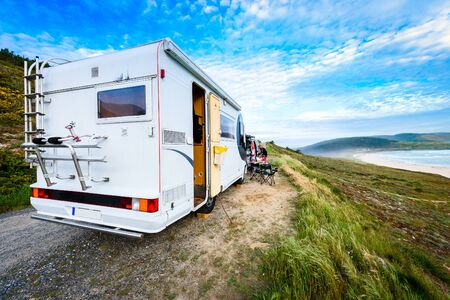 Motorhome RV and campervan are parked on a beach. Family on vacation is sitting outsides on camping chairs and table having dinner, with amazing view of the beach and ocean. Atlantic beach - Spain.