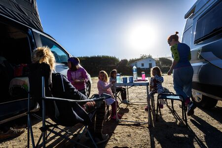 Motorhome RV or campervan is parked on a beach. Family on vacation is sitting outsides on camping chairs and table eating breakfast, with amazing view of the beach and ocean. Atlantic beach - Spain.