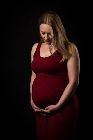 Pregnant woman in red dress holding belly on black background. Portrait of excited, happy, blond, young woman in pregnant studio shoot. Concept of maternity and expectation. Isolated black background. 写真素材