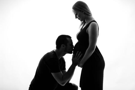Silhouette portrait of Husband man kissing pregnant woman belly. Young pregnant couple in love expecting child, studioportrait. Silhouette isolated white background.