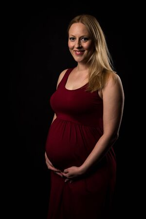 Pregnant woman in red dress holding belly on black background. Portrait of excited, happy, blond, young woman in pregnant studio shoot. Concept of maternity and expectation. Isolated black background.